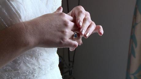 a close up of the brides hands as she plays with her silver ring. it has a blue stone and is made from the ashes of her mum who can't be at the wedding at abels harp