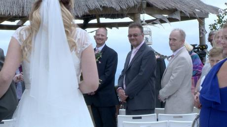 the groom sees his bride for the first time and grins as she walks down the aisle at their outdoor ceremony at abels harp