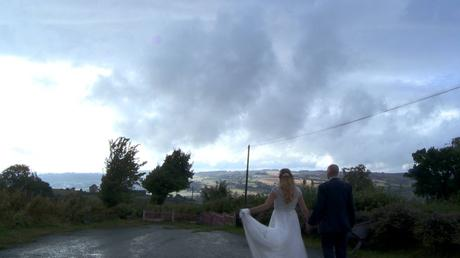 the bride holds her dress up as the married couple go for a walk towards the welsh hills. dark, dramatic clouds hover above them