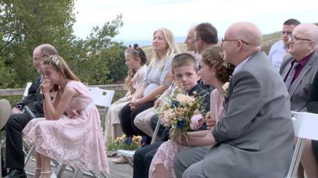 the wedding videographer caught a shot of the bride and grooms children crying and getting emotional during their outdoor ceremony