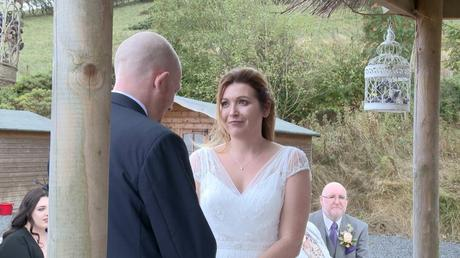 the bride looks lovingly at her husband for the wedding video during their outdoor ceremony