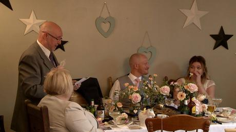 the bride wipes tears away sat at the top table as her dad gives his wedding speech