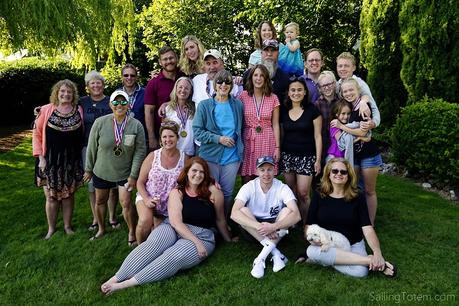A large family groups together in a lush backyard for a reunion portrait
