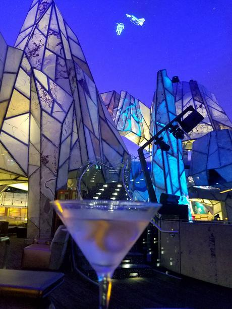 Martini in foreground, Vista Lounge in background, Space Shuttle and astronaut projected on dome