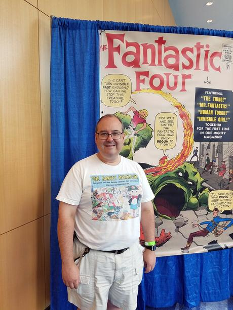 Jonathan Sternfeld standing in front of poster-sized cover of Fantastic Four # 1