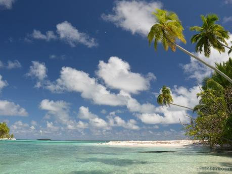 tropical island paradise: blue sky, white clouds, sandy beach, turquoise water