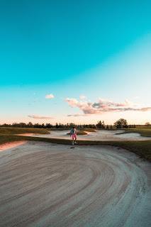 golfer raking bunker
