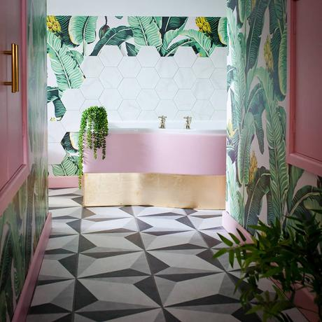 Pink and green tropical bathroom decor. Banana leaf wallpaper with monochrome patterned floor tiles