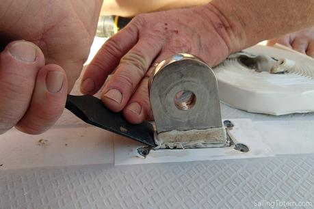 using a chisel to force butyl tape around the chainplate deck fitting