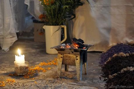 Candle, charcoal brazier, and marigold petals at an altar