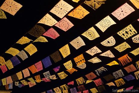 Strings of papel picado, or cut paper, garlands hung across a road