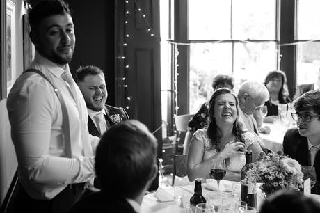 bride and groom laugh at the best mans speech