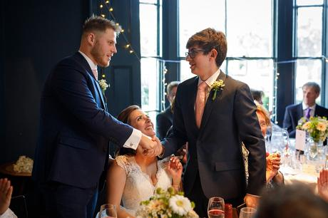 the groom shakes hands with the brides brother