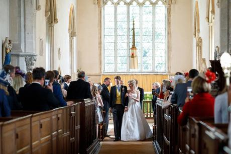bride and groom in the aisle of dennington church