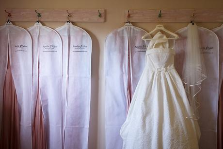 wedding dress hanging with the bridesmaids dresses
