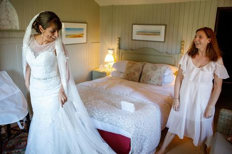 the bride shares a joke with her bridesmaid