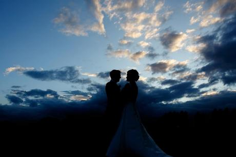 the bride and groom silhouetted against the sunset