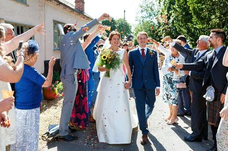 bride and groom walk through the confetti at their old buckenham wedding
