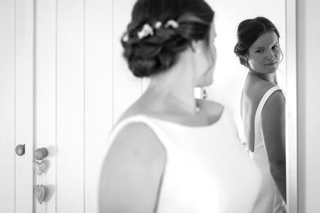 the bride checks herself in the mirror