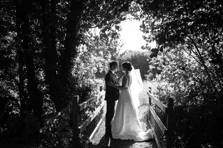 bride and groom in the grounds of old buckenham church