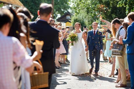 bride and groom walk through the confetti at their summer wedding