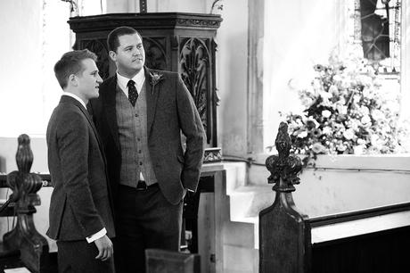 the groom and best man watch their guests arrive