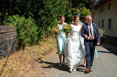 the bride and her father walk to old buckenham church