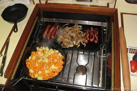 Stove with a skillet of root vegetables on the front burner and a griddle with sausages and onions  across the back