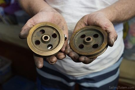 Jamie holding two steering cable sheaves in dirty, work-hardened hands