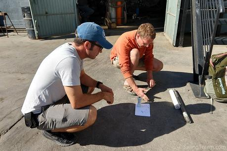 Salvador and Jamie squatting on the ground with materials and plans for anchor rollers