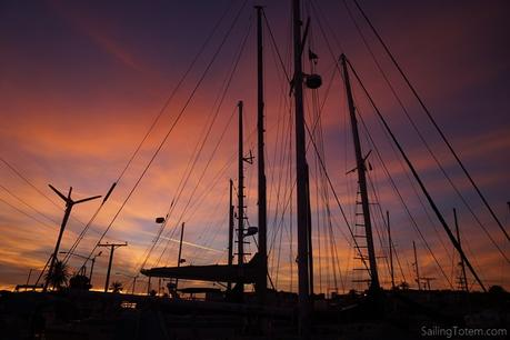 Masts and rigging from boats in the shipyard are silhouetted by a vibrant sunset in Puerto Penasco