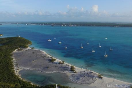boats at anchor in tropical blue water off a beautiful beach on a lush Bahamian island