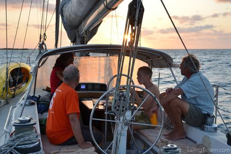 four peole in the cockpit of a sailboat, photo looking forward with the sun approaching an ocean horizon
