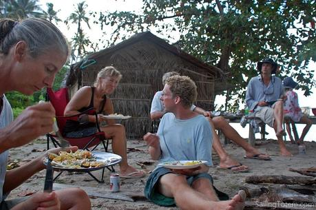 People sitting around a campfire for a potluck on an Indonesia beach.