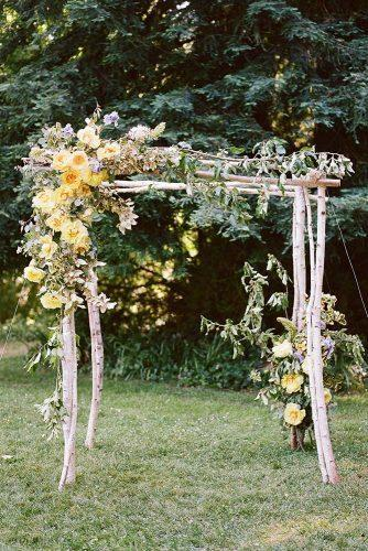 wedding colors 2019 mustard yellow flowers and greenery on rustic wooden bridal arch christina mcneill