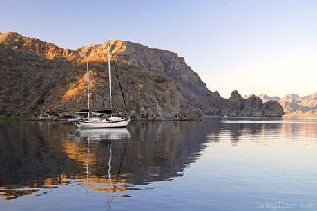 sailboat at anchor next to stunningly rugged desert coastline in Baja