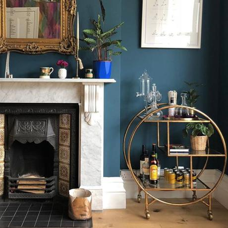 Dark and moody living room with gold luxe drinks trolley by Audenza. Image by @southlondonhome