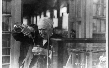 Image: Thomas Edison, half-length portrait, facing left and looking down into glass, experimenting in his laboratory, by Library of Congress/Public Domain on Picryl