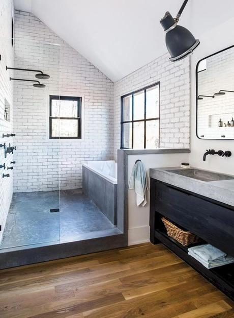 modern industrial bathroom with black vanity and concrete countertop and matte black sink hardware