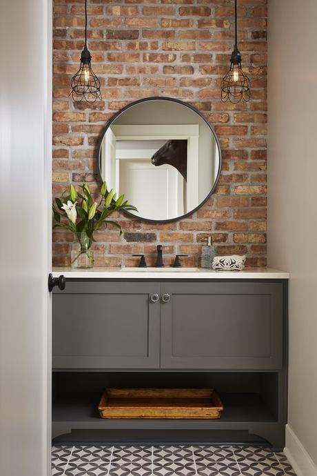 basic gray single sink bathroom vanity with brick accent wall and circle bathroom mirror