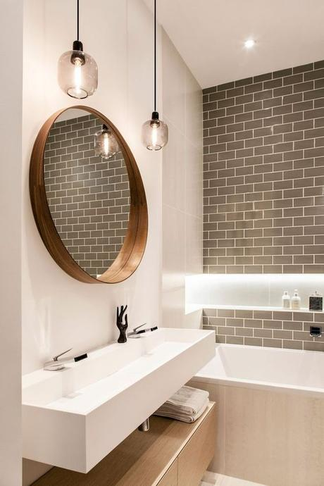 white single sink bathroom vanity with round mirror and pendant lights gray tile