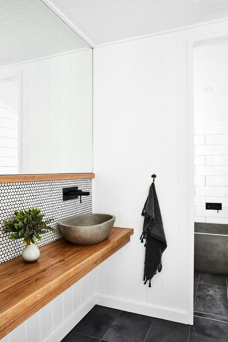 simple Scandinavian inspired modern bathroom with single sink natural wood vanity and matte black sink hardware