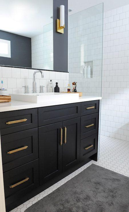 black bathroom single sink vanity with gold cabinet hardware and walk in shower