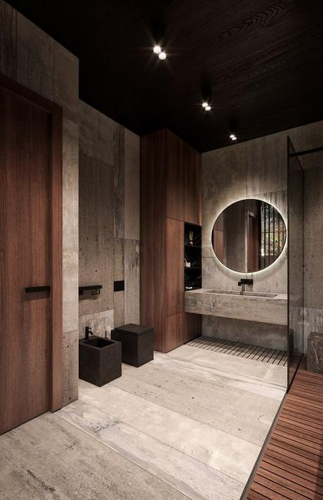 big bathroom with natural wood and concrete finishes with a concrete vanity, round mirror, and matte black sink hardware