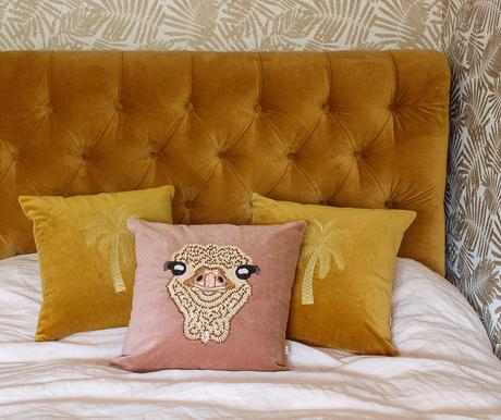 Mustard velvet bed with pink and mustard velvet scatter cushions by Audenza.