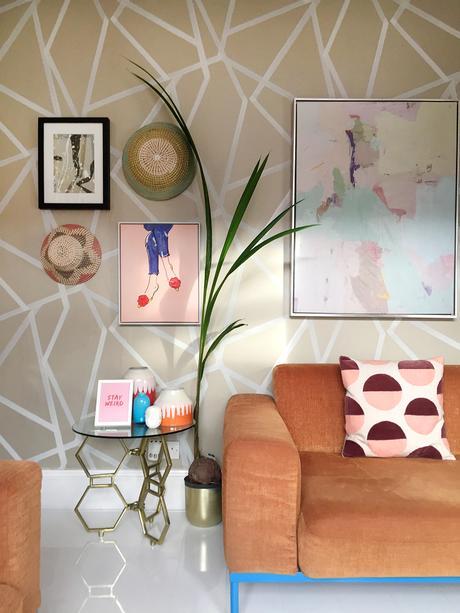 Geometric wallpaper and stunning orange velvet sofa.