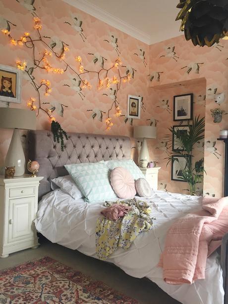 Feminine blush pink bedroom decor with 'Cranes in Flight' wallpaper by Harlequin.