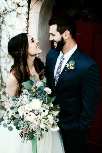 sage green wedding boutonniere and a bouquet in the photo with the happy bride and groomjessie schultz photography