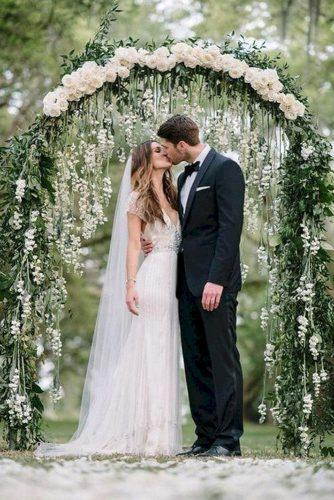sage green wedding backdrop with handing white roses and greenery arch sean money + elizabeth fay