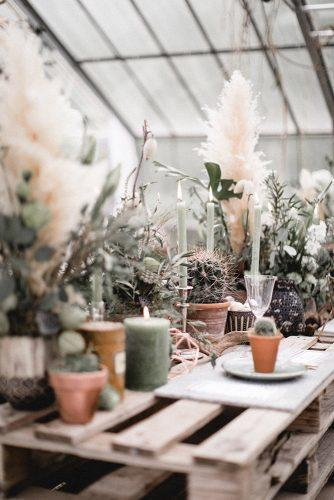sage green wedding boho centerpieces with candles pampas grass and cactus on pellet table andreas nusch hochzeitsfotografie